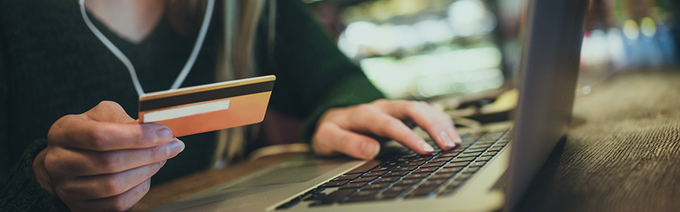 girl on computer using her credit card