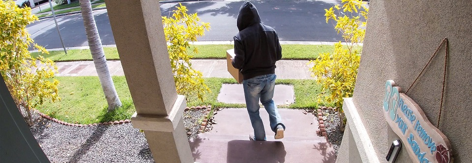 person in a hoodie walking away from a home with a package
