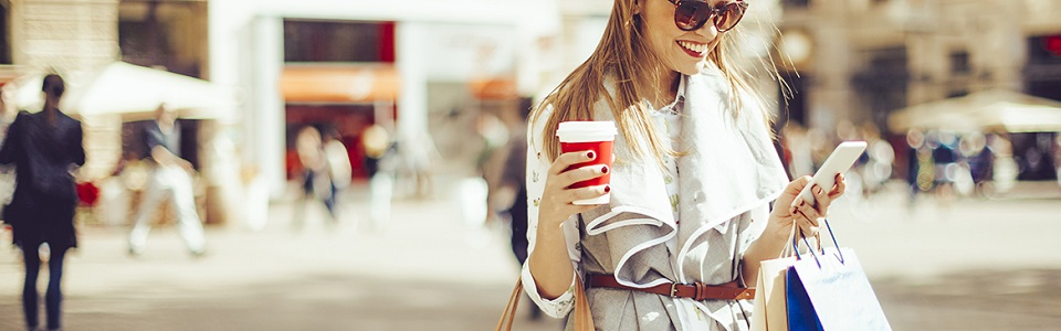 woman on mobile device with coffee cup in hand