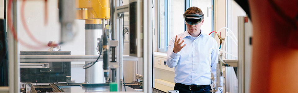 Man in an industrial space looking through AI glasses
