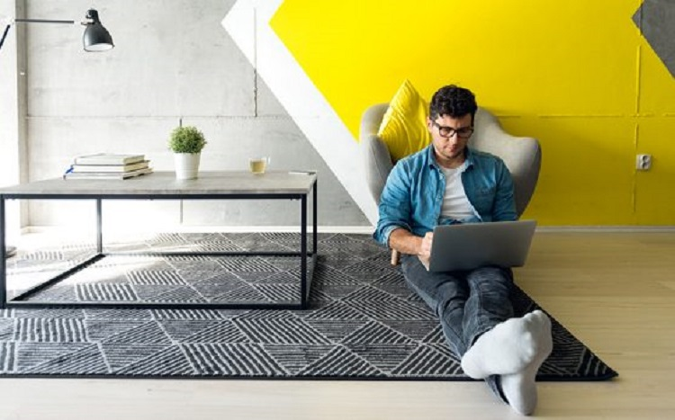 Man sitting on floor working on his laptop from home