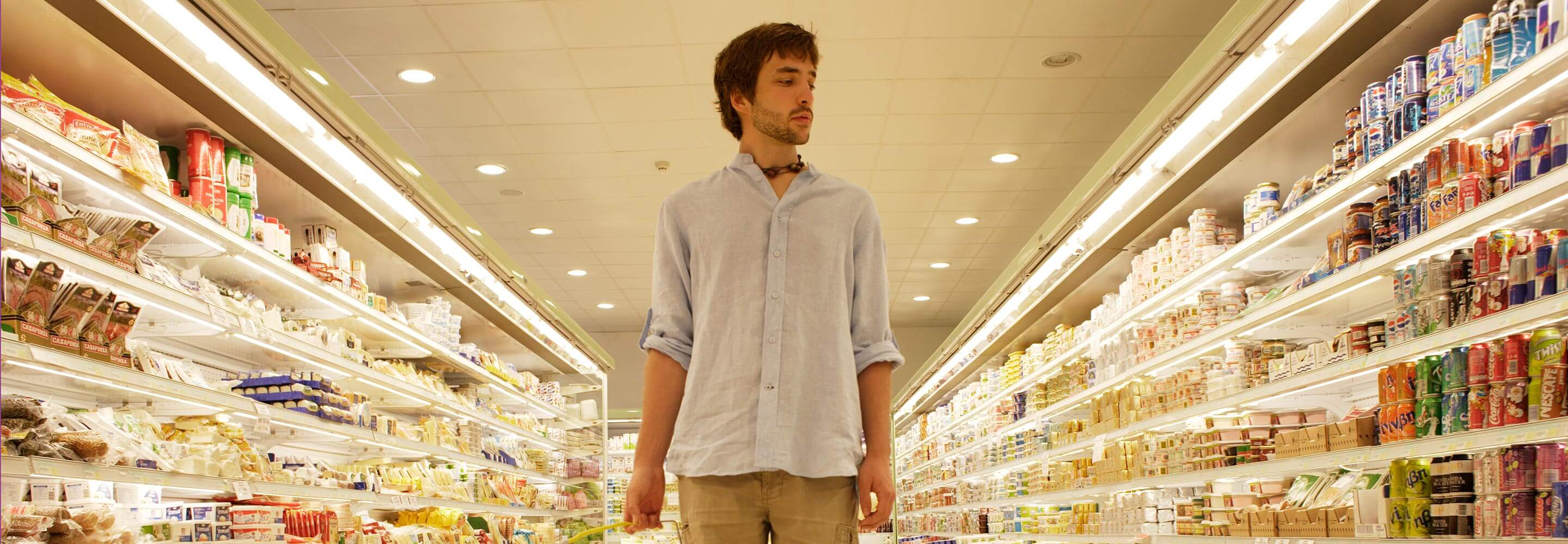 Man at the isle in the supermarket deciding what to buy