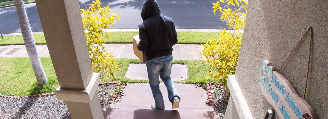 Package thief caught on video doorbell system stealing a box delivery from the front step of a suburban home