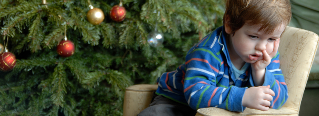 Little boy sitting on sofa next to Christmas tree