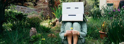 Person sitting in garden wearing a box on head