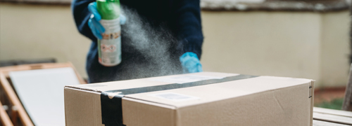 man disinfecting a package