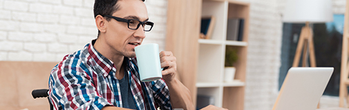 Man sitting in front of laptop drinking coffee