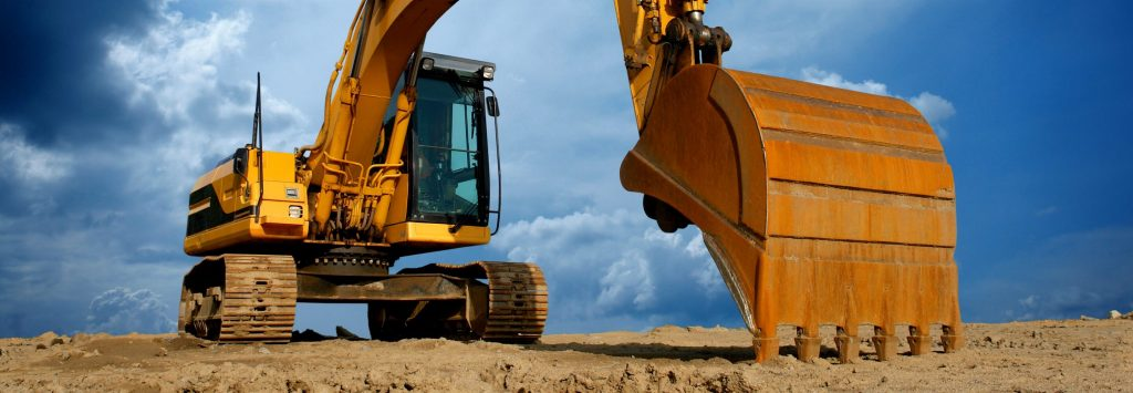 Big yellow excavator digging dirt