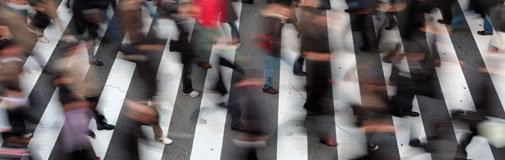 blurred image of a crowd of people crossing the street