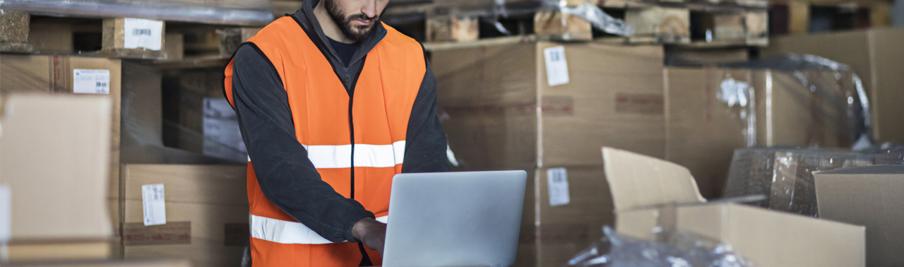 man in shipping warehouse on laptop