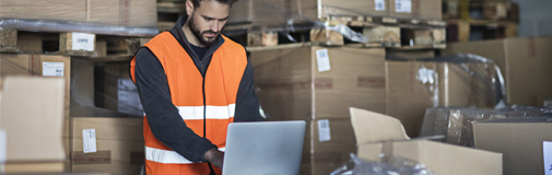 man in warehouse on laptop