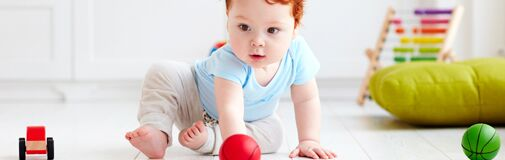 Toddler looking at a red ball