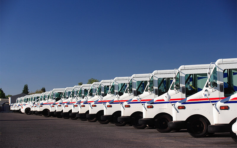 Row of USPS postal delivery trucks