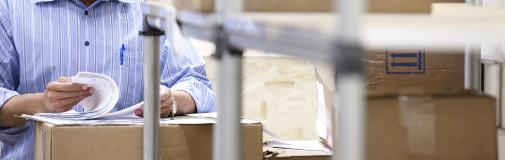 man in warehouse with papers