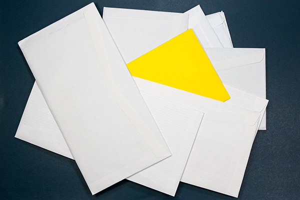 stack of white envelopes with one yellow envelope