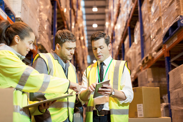 men looking at a tablet in a warehouse