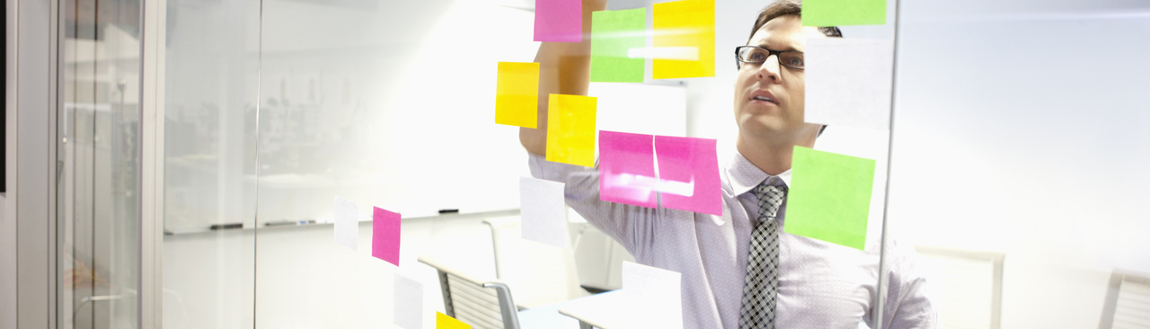 man looking at sticky notes on a glass wall