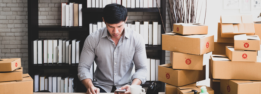 man in home office with stacks of boxes for shipping around him