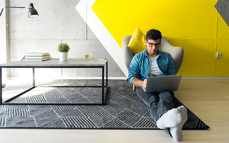 Man sitting on floor of casual office, working on a laptop