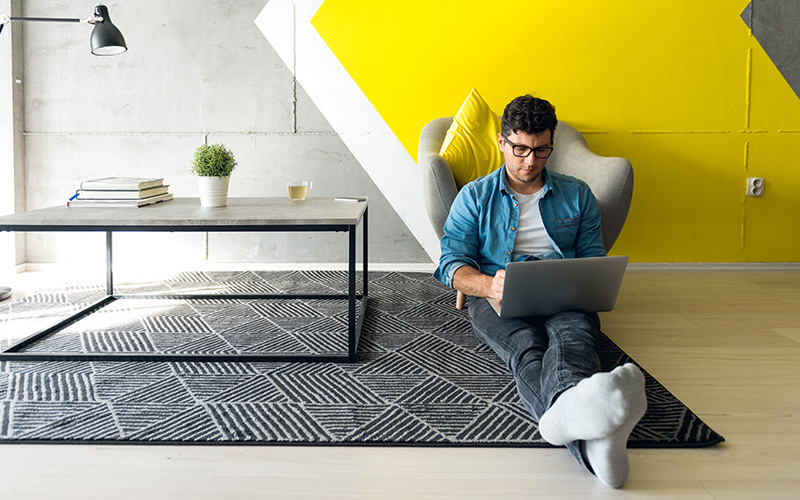 man sitting on the floor of a home office working on a laptop